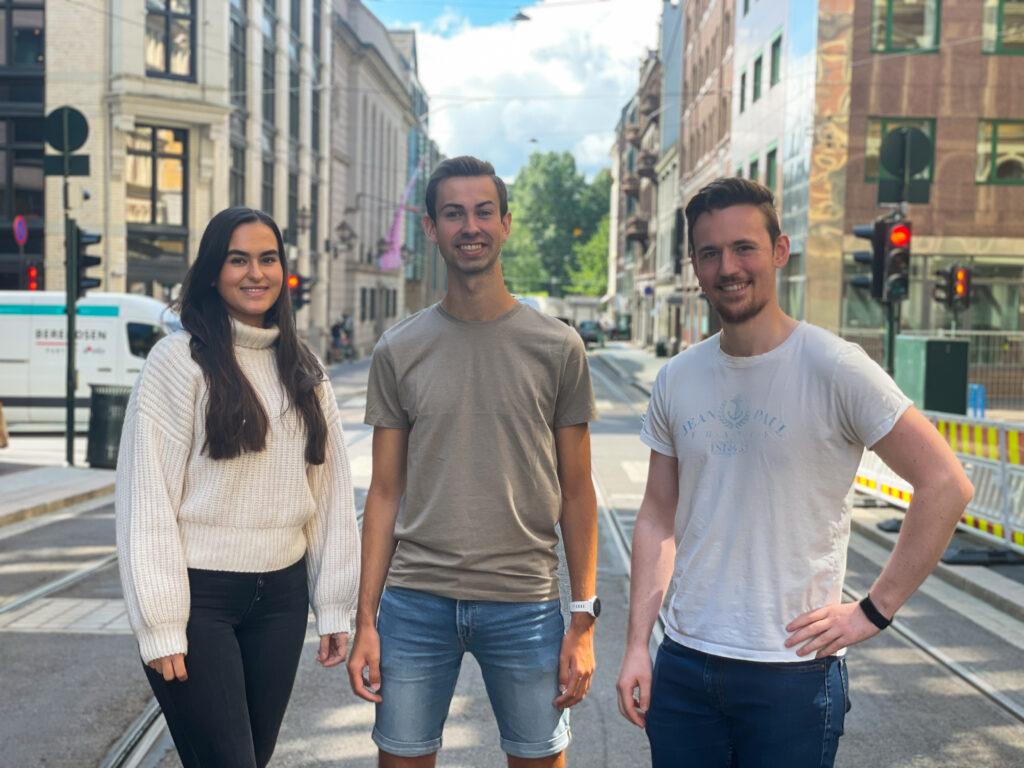 Three interns standing beside eachother in the middle of a street